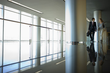 Businesswoman and businessman walking in large modern lobby, reflection on shiny floor