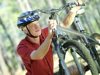 Active senior man in cycling helmet checking bicycle, close-up (tilt)