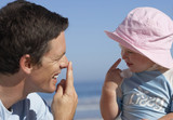 Father and daughter (2-4) playing on beach, touching noses with fingers, smiling, side view