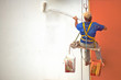 Hanging Painter painting wall with roller