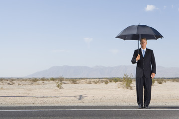 Businessman with umbrella on open road in desert, portrait, low angle view