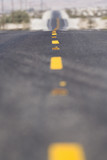 Close-up of lines in middle of road in desert