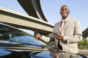Businessman with electronic organiser by car and overpasses, portrait