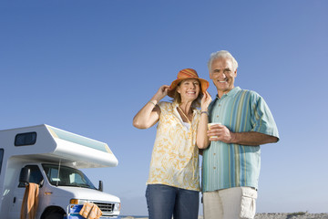 Mature couple by motor home on beach, smiling, portrait, low angle view