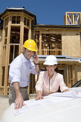 Man and woman in hardhats looking at blueprint by partially built house, man on mobile phone