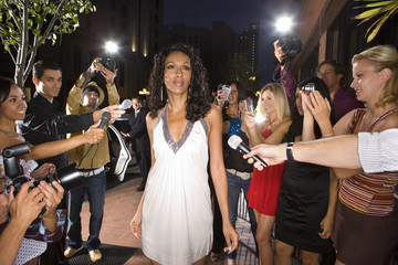 Young woman surrounded in press and paparazzi