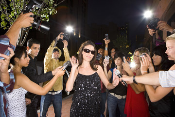 Paparazzi taking photographs of young woman in sunglasses, low angle view