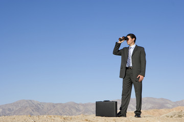 Businessman with briefcase using binoculars in desert