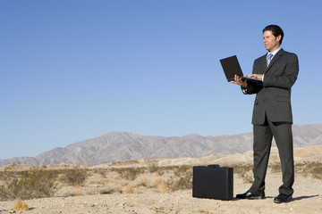 Businessman by briefcase using laptop computer in desert, low angle view