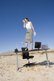 Businesswoman standing on desk in desert, shouting into telephone receiver, low angle view