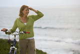 Mature woman with bicycle by sea, looking into distance