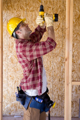 Builder in hardhat drilling in partially built house