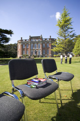 Books and pens on chair on grass by manor house