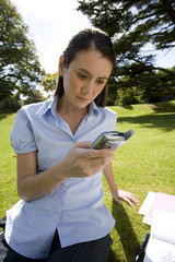 Woman on grass with paperwork, using mobile phone