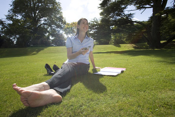 Woman on grass with mobile phone and paperwork, smiling, low angle view