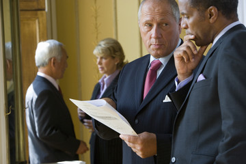Mature businessman showing paperwork to colleague, close-up