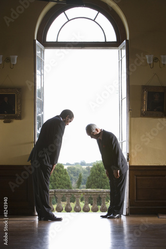 Two businessmen looking down by open window, side view