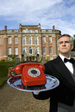 Mature butler with telephone on tray by manor house, low angle view