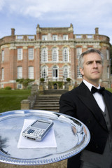 Mature butler with mobile phone on tray by manor house, low angle view