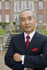 Mature businessman with arms crossed in front of manor house, portrait, close-up