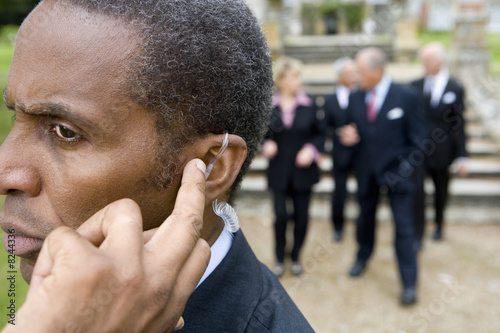 Man with hand on earpiece by manor house, businessmen and women in background, close-up