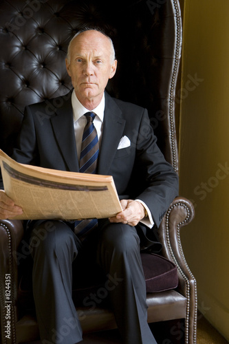 Senior man reading newspaper in armchair, portrait