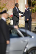 Businessman and colleague shaking hands by chauffeur holding door of car open (differential focus)