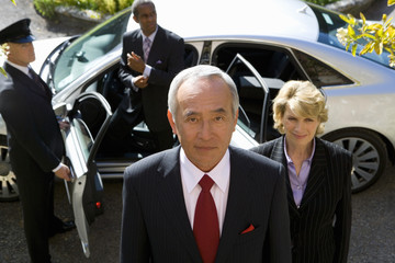 Businessman and colleagues getting out of car, chauffeur holding door open, portrait