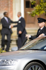 Chauffeur holding door of car open, businessmen shaking hands in background
