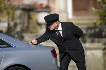 Chauffeur polishing back of car outdoors