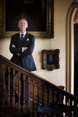 Businessman on stairs, arms crossed, portrait, low angle view