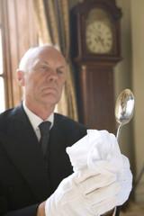 Butler polishing spoon, low angle view