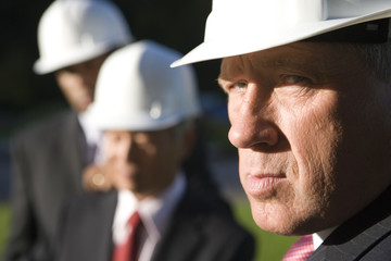 Small group of businessmen in hardhats, portrait, close-up