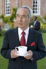 Mature businessman with teacup outdoors