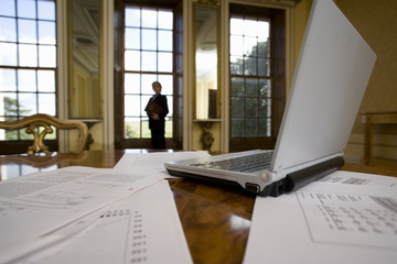Laptop computer and paperwork on table, woman by window in background, low angle view