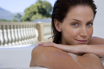Young woman in bath, smiling, portrait, close-up