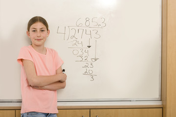 Girl (10-12) by equation on whiteboard in classroom, portrait