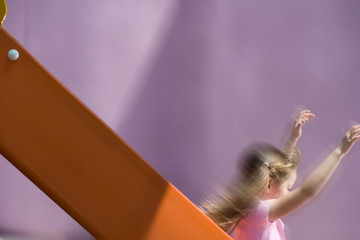 Girl (5-7) on slide, side view (blurred motion)