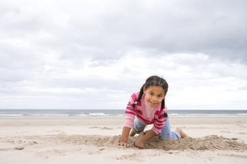 Girl (5-7) digging hole on beach, smiling, portrait