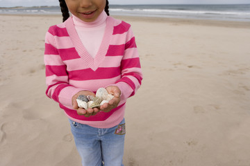 Girl (7-9) with shells on beach, mid section