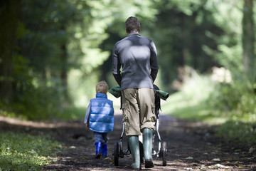 Father and son (2-4) wearing wellington boots, walking along woodland path, side by side, rear view, man pushing baby stroller (differential focus)