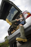 Boy (8-10) putting on wellington boots, sitting in boot of stationary car, smiling, portrait, low angle view (tilt)