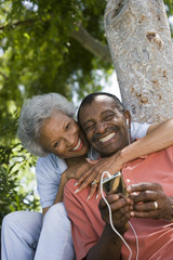Senior couple sitting in garden, man listening to MP3 player, leaning against tree trunk, smiling, woman embracing man, portrait