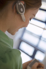 Woman wearing mobile phone hands-free device on ear, side view, close-up (tilt, differential focus)