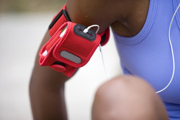 Female jogger wearing MP3 player strapped to arm in red case, mid-section, close-up, front view (differential focus)