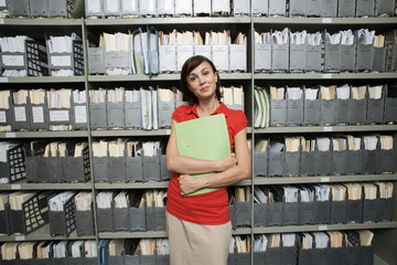 Woman wearing red top, standing in office archive, carrying file, smiling, front view, portrait