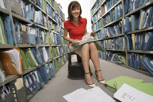 Woman wearing skirt, high heels and red top, sitting on footstool in aisle of office archive with file in lap, smiling, documents on floor