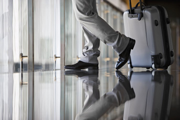 Businessman leaving lobby with luggage, side view, low section, surface level, reflection on floor
