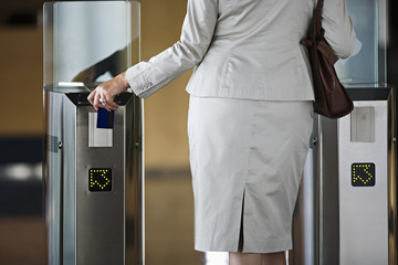 Businesswoman swiping card in entrance barrier, rear view, mid-section