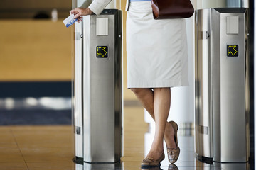 Businesswoman swiping card in entrance barrier, rear view, low section